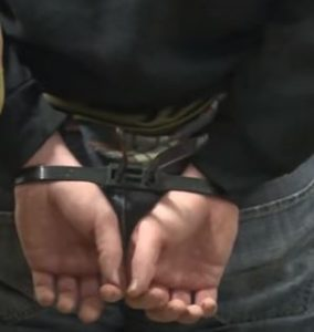 Man arrested and handcuffed