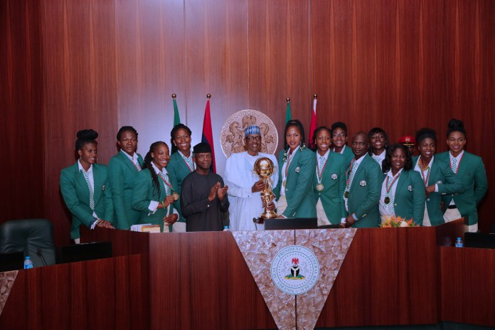 President Muhammadu Buhari, Vice President Yemi Osinbajo and the Victorious Nigerian Female Basketball Team D'Tigress with the Cup won at the 2017 FIBA Women's Afrobasket recently. (Image credit: Sunday Aghaeze/State House, 30 August 2017)