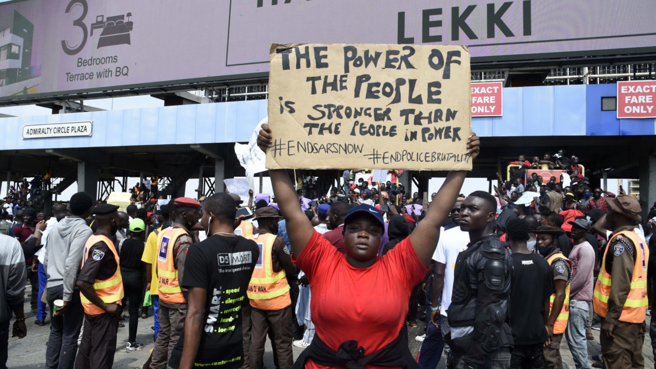 #EndSARS: A demonstrator holds a placard to protest against abuses by the Special Anti-Robbery Squad (SARS) at the Lekki toll Plaza in Lagos, on October 12, 2020. (Photo by PIUS UTOMI EKPEI/AFP)