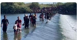 Thousands of migrants walking across a dam in the Rio Grande, heading to Del Rio International Bridge in South Texas (Foxnews/@BillFOXLA)